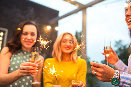 Photo for Group of partying girls with flutes with sparkling wine and bengal fire having fun on the party - Royalty Free Image