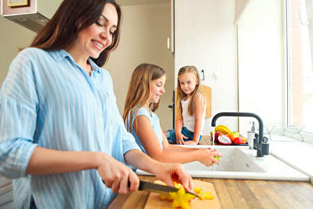 Photo pour Beautiful little girls with they mother in the kitchen preparing a fresh fruit salad - image libre de droit