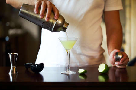 Photo for Barman at work, preparing cocktails. Pouring martini to cocktail glass. Service and beverages concept - Royalty Free Image