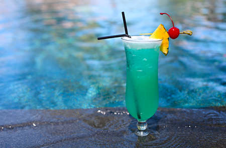 Foto de Glass with a bright blue lagoon cocktail by the pool. Luxury resort on tropical island - Imagen libre de derechos