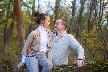 Photo pour Beautiful couple sitting together on the tree in park hugging - image libre de droit