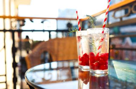 Foto de Summer refreshing lemonade with rasberry on a balcony of terrace, paper straw on the glasses. Sunset - Imagen libre de derechos