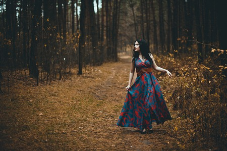 Photo for Red Hooded Woman Holding Apple Fairytale Portrait - Fairytale image of a beautiful  girl wearing a red hood near the forest - Royalty Free Image