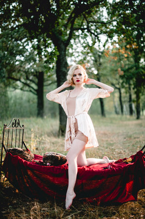 Photo pour Beautiful and elegant blonde woman with red lips and hair waves wearing wine red nightie posing on the bed outdoors, retro vintage style and fashion - image libre de droit