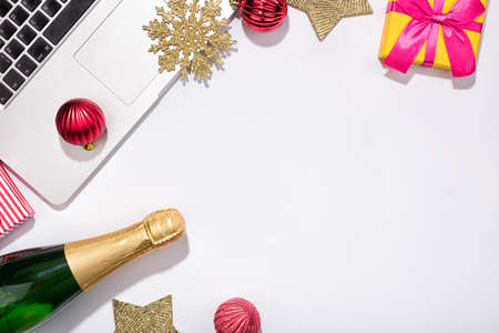 Foto de Workspace with Red baubles and tree branches. Christmas holidays composition with bottle of champagne on white background with copy space for your text - Imagen libre de derechos
