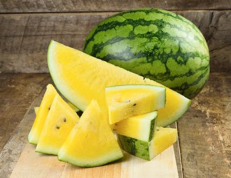 Photo pour Yellow watermelon  sliced on wooden background - image libre de droit