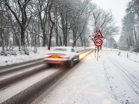 fast moving car brakes as it passes a speed restriction sign in a snow storm under morning light