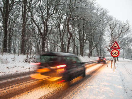 fast moving van brakes as it passes a speed restriction sign in a snow storm under morning light