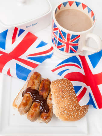British sausage sandwich on a sesame bun with brown sauce cup of tea in a union jack mug, butter dish and british union jack flags on white table