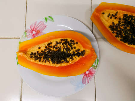 Photo for Delicious papaya cut in half. Tropical exotic fruit of orange color, of smooth flavor, with black seeds. Carica papaya plant produce. - Royalty Free Image