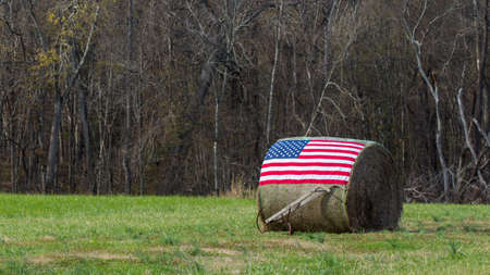 Photo pour American flag on bale of hay with hand plow in front - image libre de droit
