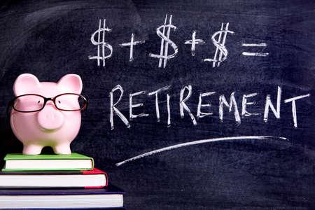 Foto de Pink piggy bank with glasses standing on books next to a blackboard with simple retirement formula.  Sharp focus on the piggy bank. - Imagen libre de derechos
