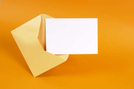 Photo pour Metallic gold envelope with blank message card letter or invitation isolated on an orange background.  - image libre de droit