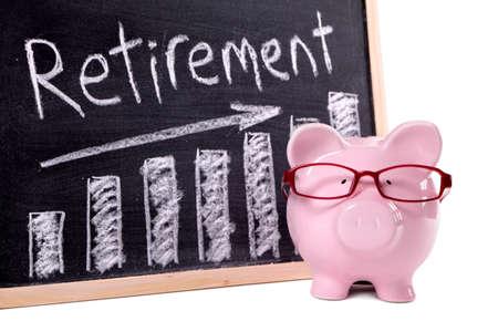 Foto de Pink piggy bank with glasses standing next to a blackboard with retirement savings message.  Sharp focus on the piggy bank. - Imagen libre de derechos