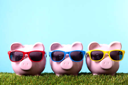 Photo pour Three pink piggy banks with sunglasses on grass with blue sky - image libre de droit