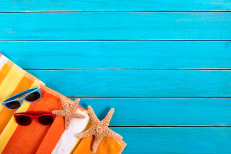 Foto de Beach scene with orange striped towel, starfish and sunglasses on old blue painted wood decking.  Space for copy. - Imagen libre de derechos