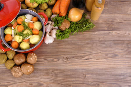Photo for Red casserole pot with organic vegetables and herbs on a wooden table with copy space. - Royalty Free Image