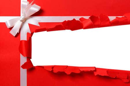 Foto de Christmas gift torn open strip, white ribbon bow, red wrapping paper background, copy space - Imagen libre de derechos