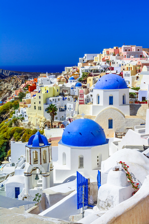 Photo for Oia town, Santorini island, Greece at sunset. Traditional and famous white houses and churches  with blue domes over the Caldera, Aegean sea. - Royalty Free Image