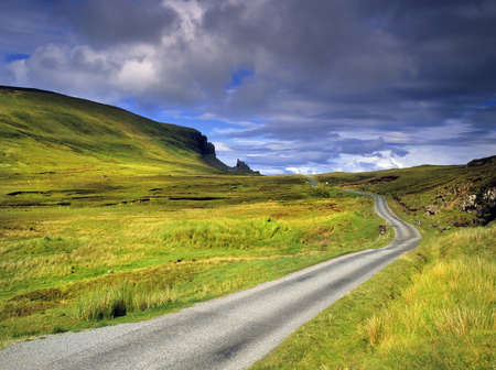 Photo for a desolate country road across moorland on the isle of syke with the quiraing in the distance - the isle of skye in Scotland, Great Britain UK - Royalty Free Image