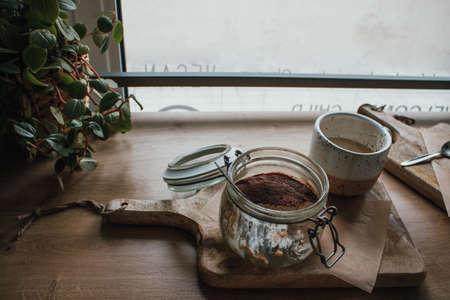 Foto de High angle view of tiramisu in glass cup with coffee cappuccino. In vegan shop, local cozy cafe. Wooden background, candid style. Copy space - Imagen libre de derechos