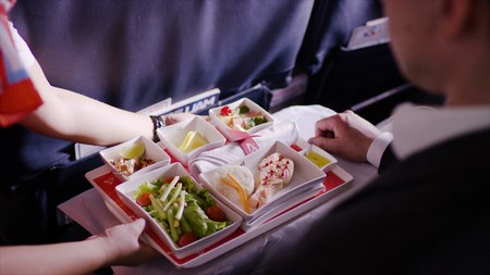 Foto de Midsection of stewardess holding tray with airplane food on blue background. Stewardess brought lunch, businessman, first class, high level of service on the plane - Imagen libre de derechos