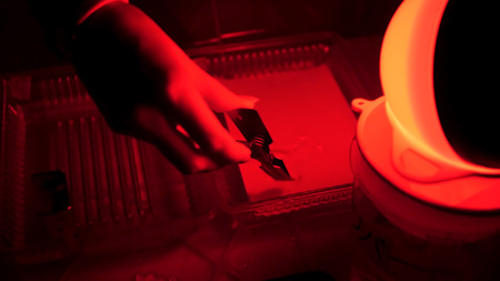 Foto de Dark room equipped under photo laboratory. Trays with reagents for printing by hand. Darkroom printing process photographer using enlarger to produce photographic prints. Working in a red dark room. - Imagen libre de derechos