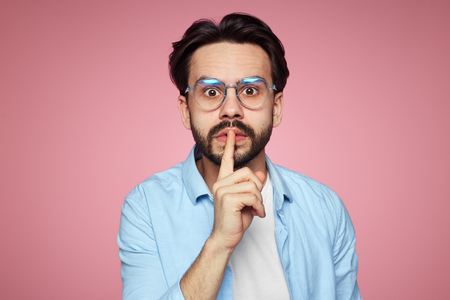 Photo for Fashionable hipster guy demands keeps silence, shows hush gesture, looks with stunned expression at camera, afraids of gossiping, isolated over pink background. Mute man - Royalty Free Image