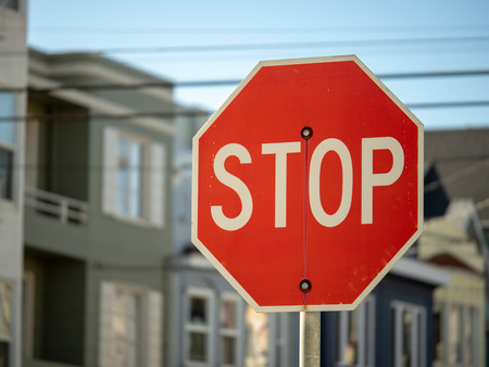 Foto de A stop sign in a residential neighborhood with copy space to the left on a sunny day - Imagen libre de derechos