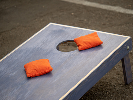 Photo pour Orange beanbags sitting on blue cornhole board platform - image libre de droit
