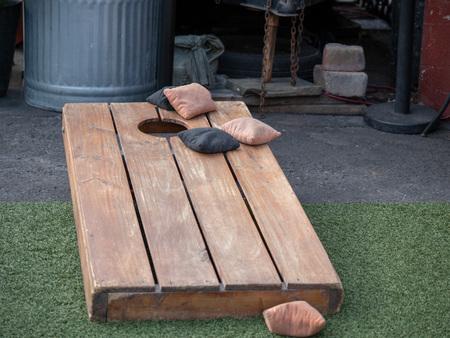 Foto de Sets of beanbags in competitive game of cornhole on a lumber platform - Imagen libre de derechos