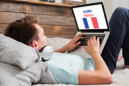 Photo pour Young man using a laptop for learning french while lying in the bed at home. - image libre de droit