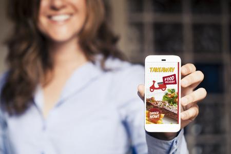 Photo pour Take away food mobile phone app in a mobile phone screen. - image libre de droit