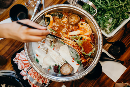 Photo for Korean hot pot meal. Hands taking food with chopsticks. - Royalty Free Image