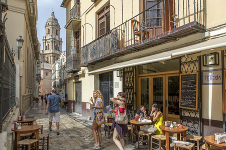 Photo for MALAGA, SPAIN - September 2nd, 2018: Tourists having a tea in a coffee shop with the Cathedral in the background, during a journey in the city center of Malaga, Spain. - Royalty Free Image
