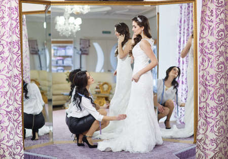 Photo for Female trying on wedding dress in a shop with women assistant. - Royalty Free Image
