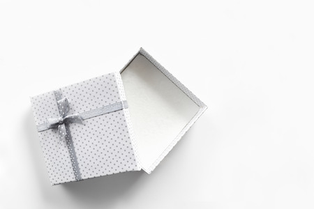 Foto de White empty gift box with small circles gray fabric tape with gray tie. Isolated white top view - Imagen libre de derechos