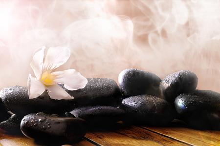 Foto de Group of black stones on wood base, steam background. Sauna, therapy, relaxation, and health concept. - Imagen libre de derechos
