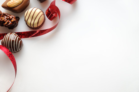 Photo for Assorted bonbons black and white chocolate with nuts and red ribbon on a white table. Top view. Close up. Horizontal composition. - Royalty Free Image