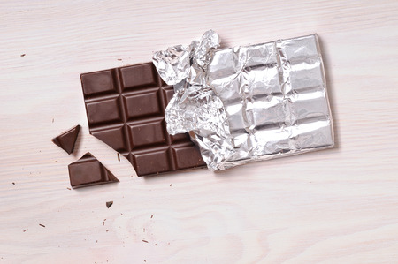 Photo for Chocolate bar with silver wrapping on a wooden table with a broken portion. Horizontal composition. Top view - Royalty Free Image