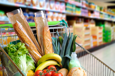 Photo for Shopping cart full of food in the supermarket aisle. High internal view. Horizontal composition - Royalty Free Image