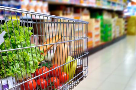 Photo pour Shopping cart full of food in the supermarket aisle. Side tilt view. Horizontal composition - image libre de droit