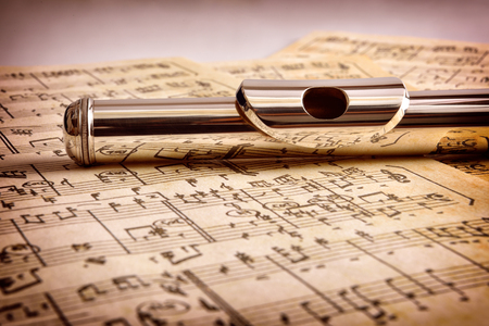 Photo for Mouthpiece of flute on old handwritten sheet music close up. Horizontal composition. Front view - Royalty Free Image