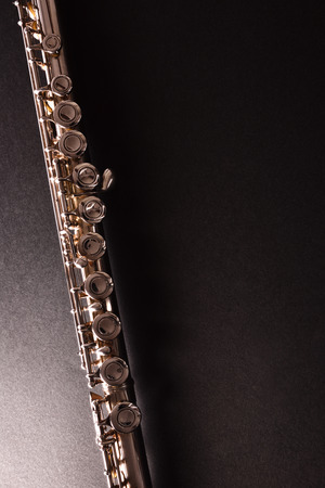 Photo for Detail of tansverse flute on black table. Vertical composition. Top view - Royalty Free Image
