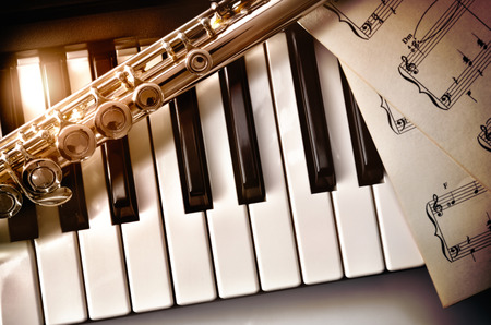 Photo for Piano and flute with golden shine and sheet music. Horizontal Composition.Top view - Royalty Free Image