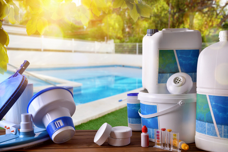 Foto de Swimming pool service and equipment with chemical cleaning products and tools on wood table and pool background. Horizontal composition. Front view - Imagen libre de derechos