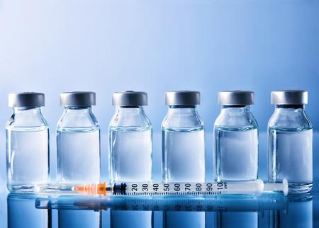 Foto de Row of vials with medication and syringe on blue methacrylate table. Horizontal composition. Front view. - Imagen libre de derechos