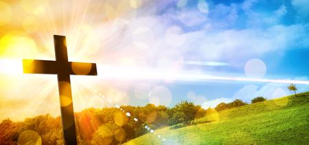 Foto de Religious illustration with backlit cross with golden glitter and bokeh and nature landscape background. Horizontal composition - Imagen libre de derechos