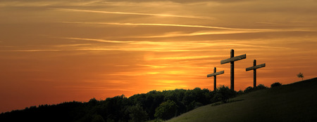 Foto de Religious illustration with three backlit crosses with golden glitter and bokeh and nature landscape background. Horizontal composition - Imagen libre de derechos