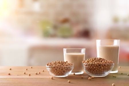 Photo pour Reptientes with soy milk and grains on a wooden table and rustic kitchen background. Alternative milk concept. Front view. Horizontal composition - image libre de droit